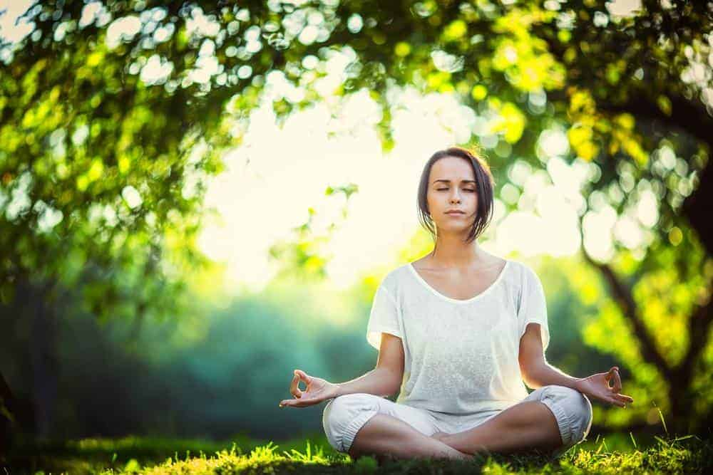 Image of a woman meditating in the park - Total Integrated Therapy